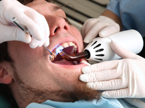 man in dental chair with dentist and assistant working on his teeth