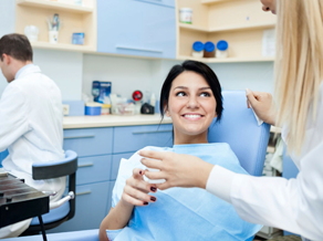 Woman in dental chair smiling, taking a glass of water from dentist
