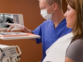 Dentist examining x-ray with patient, point at screen