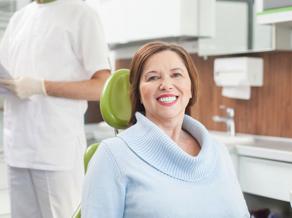 older woman smiling in dental chair