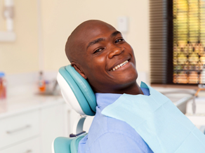 Young man in dental chair smiling, ready to begin appointment